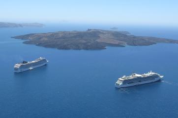 """Wanderung von der Stadt Oia (im Norden) zur Inselhauptstadt Fira, immer am Steilhang zur Caldera entlang: Kreuzfahrtschiffe ankern und warten auf """"Heimkehrer"""", dahinter der Vulkankegel. Er kann mit Schiffen besucht werden, es gibt jedoch keine Bebauung."""
